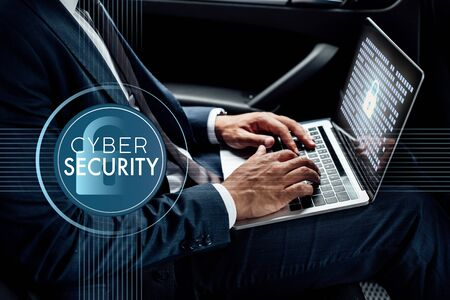 partial view of african american businessman using laptop in car with cyber security illustration 스톡 콘텐츠