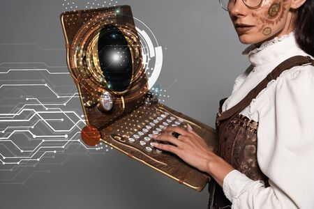 cropped view of steampunk woman using vintage laptop with glowing digital illustration isolated on grey