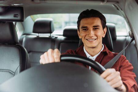 Smiling handsome man holding steering wheel of car