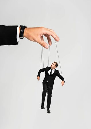 cropped view of businessman playing with marionette in suit isolated on grey