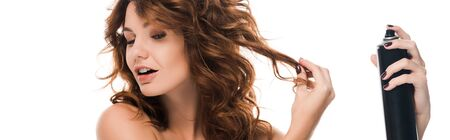 panoramic shot of attractive curly girl touching hair while holding hair spray isolated on white