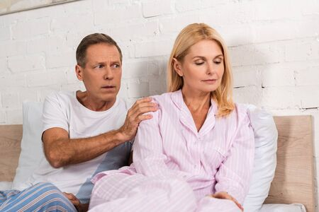 Confused man calming down offended wife on bed