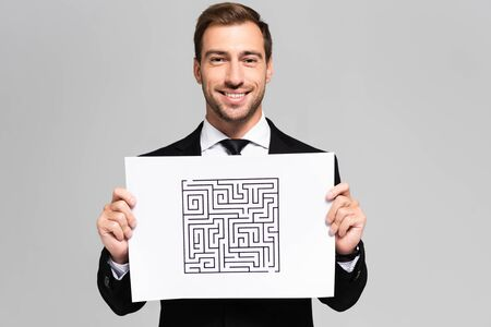 smiling and handsome businessman holding paper with labyrinth isolated on grey