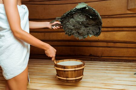 cropped view of woman in towel holding washtub and birch broom in sauna