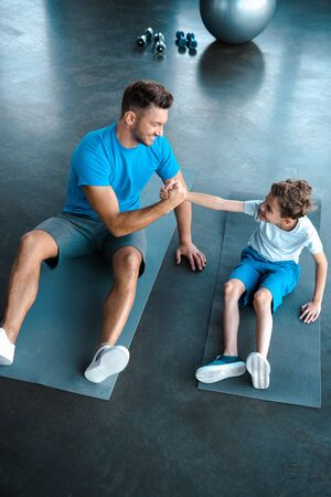 overhead view of happy father and son holding hands while sitting on fitness mats Zdjęcie Seryjne