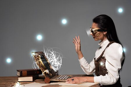 steampunk woman in goggles waving hand during video chat with glowing digital illustration isolated on grey Фото со стока