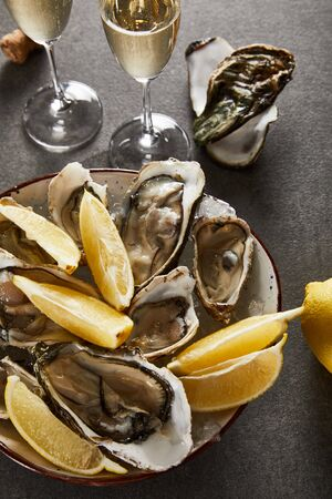 top view of delicious oysters and lemons in bowl near champagne glasses with sparkling wine on grey surface Standard-Bild