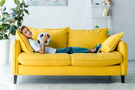 happy boy in white t-shirt lying on yellow sofa with football