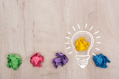top view of multicolored crumpled paper balls and light bulb illustration on wooden surface, business concept Stock Photo