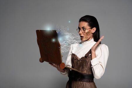 shocked steampunk woman in glasses using vintage laptop with glowing digital illustration isolated on grey