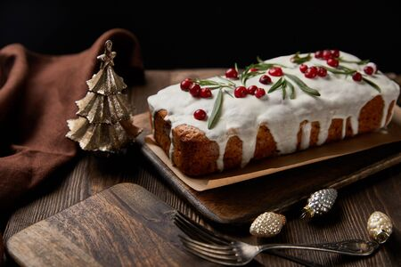 traditional Christmas cake with cranberry near baubles, forks and brown napkin on wooden table isolated on black