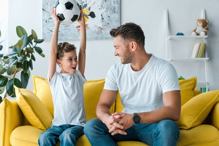 cheerful father looking at son holding football above head