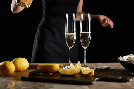 selective focus of champagne glasses with sparkling wine near woman isolated on black 版權商用圖片