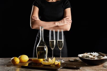 cropped view of woman standing with crossed arms near sparkling wine in bottle and oysters in bowl with ice isolated on black