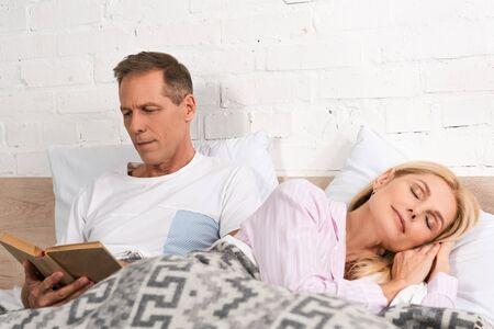 Man reading book while wife sleeping in bed Foto de archivo