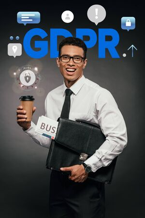 happy african american businessman holding newspaper, coffee to go and leather briefcase on dark background with gdpr illustration