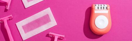 top view of disposable razors, epilator and wax depilation stripes on pink background, panoramic shot Foto de archivo - 134818132