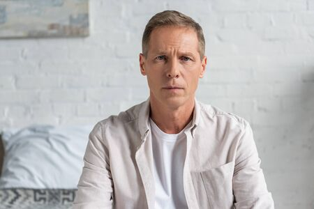 Disappointed man looking at camera in bedroom