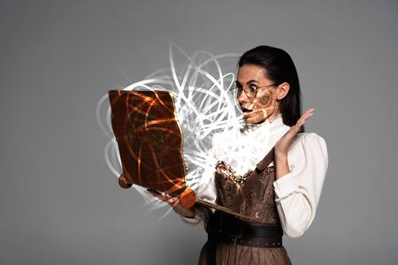 shocked steampunk woman in glasses using vintage laptop with glowing fairy illustration isolated on grey
