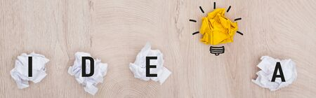 panoramic shot of crumpled paper balls, idea word and light bulb illustration on wooden surface, business concept