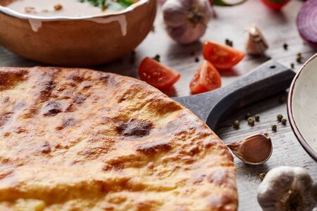 Traditional Georgian imereti khachapuri with vegetables and spices on table