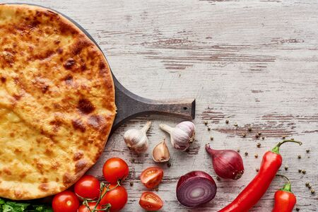Top view of Imereti khachapuri on cutting board with vegetables and spices on table Stok Fotoğraf