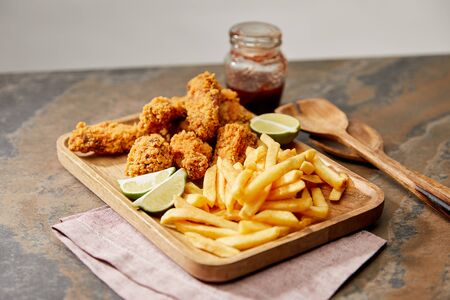 wooden board with delicious chicken nuggets, french fries and lime on stone surface isolated on grey