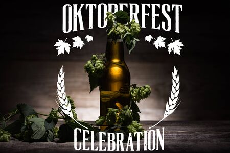 fresh beer in bottle with green hop on wooden surface in dark with white Oktoberfest celebration illustration Zdjęcie Seryjne