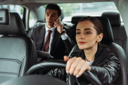 Woman taxi driver holding steering wheel while businessman talking on smartphone