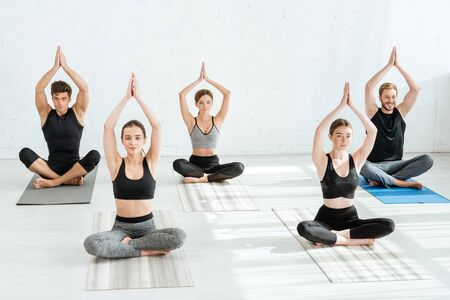 five young people meditating in half lotus pose with raised prayer hands Stock fotó