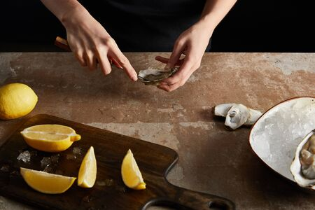 cropped view of chef holding knife while opening oyster near lemons isolated on black