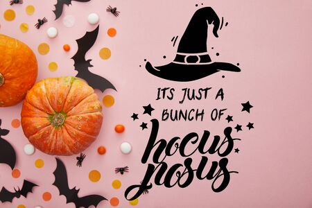top view of pumpkin, bats and confetti on pink background with its just a bunch of hocus pocus illustration