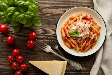 top view of tasty bolognese pasta with tomato sauce and Parmesan in white plate near ingredients and cutlery on wooden table