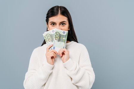 pretty girl in white sweater holding euro banknotes near face isolated on grey Фото со стока