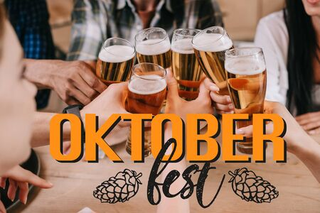 cropped view of multicultural friends clinking glasses of beer near Oktoberfest illustration