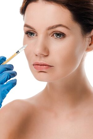 cropped view of plastic surgeon in latex glove holding syringe near attractive naked girl isolated on white