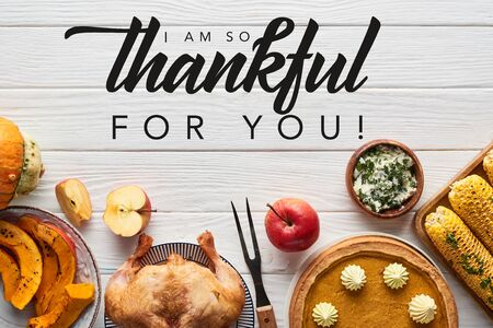 top view of roasted turkey, pumpkin pie and grilled corn served on white wooden table with i am so thankful for you illustration