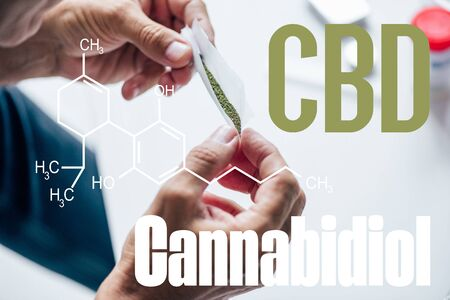 cropped view of man holding blunt of medical cannabis with cbd molecule illustration
