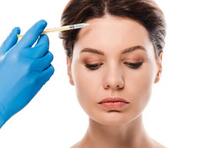 cropped view of plastic surgeon in blue latex glove holding syringe near attractive woman isolated on white 免版税图像