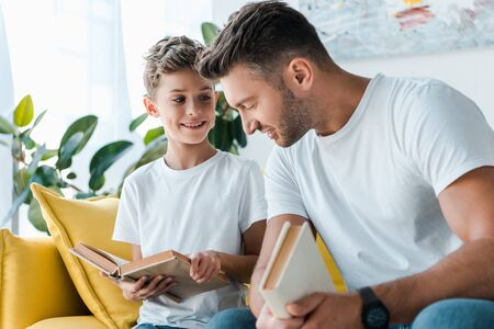 selective focus of happy father and son holding books