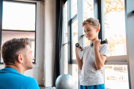 selective focus of happy father looking at son weightlifting dumbbells