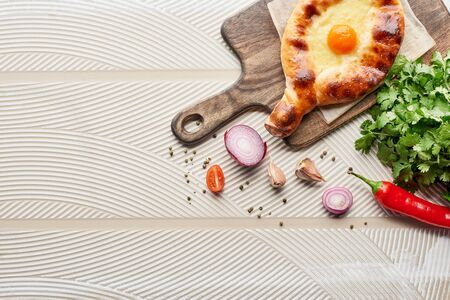 Top view of adjarian khachapuri with vegetables and cilantro on textured background