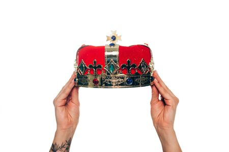 cropped view of woman holding red crown, isolated on white