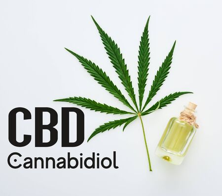 top view of cannabis leaf and cbd oil on bottle on white background with cbd illustration