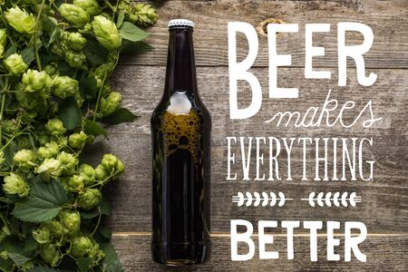 top view of fresh beer in bottle with green hop on wooden surface with white beer makes everything better illustration Zdjęcie Seryjne