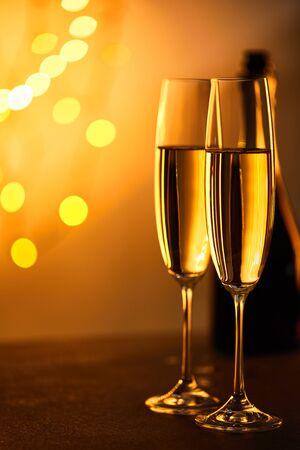 Gläser Champagner mit verschwommener Flasche und gelber Weihnachtsbeleuchtung