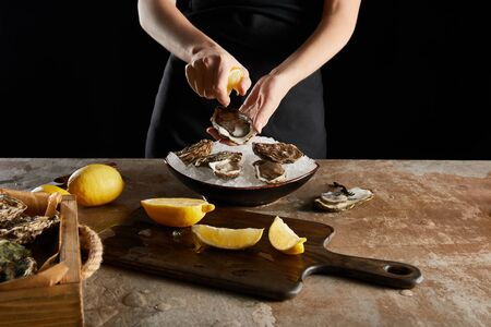 cropped view of woman squeezing lemon on oyster isolated on black 版權商用圖片