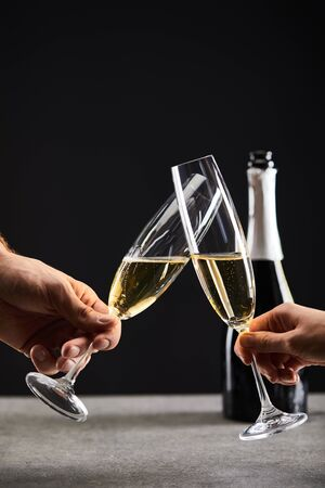 cropped view of couple clinking with glasses and celebrating christmas, on black with bottle of champagne Stock Photo