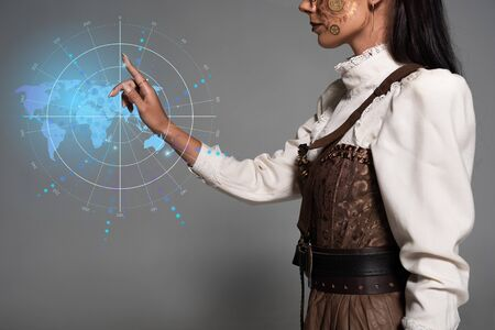 cropped view of steampunk young woman pointing with finger at digital map illustration Фото со стока