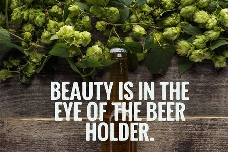 top view of fresh beer in bottle with green hop on wooden surface with beauty is in the eye of the beer holder illustration Zdjęcie Seryjne
